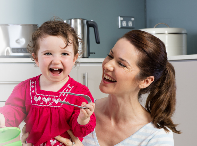 Mother and toddler laughing in the kitchen